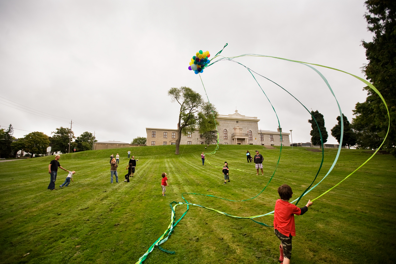 image of children and adults playing with a large bunch of colourful helium balloons with a tail of green streamers