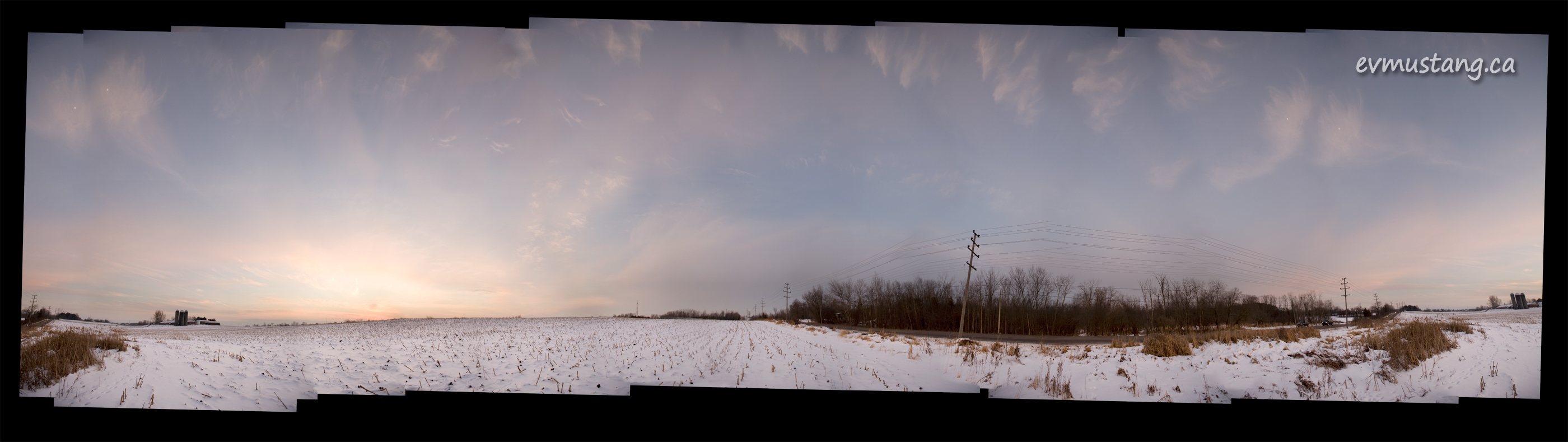 panoramic image of sunset over filed covered in snow