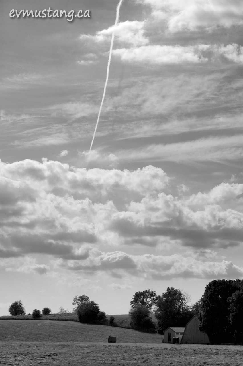 black and white image of vapour trail in cloudy sky over farm field
