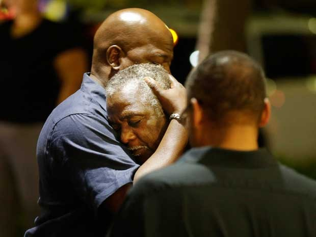 Membros da igreja atacada em Charleston se abraçam após tiroteio. (Foto: David Goldman / AP Photo)