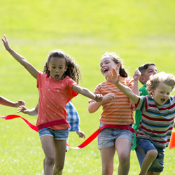 Group of children running through the ribbon to finish the race