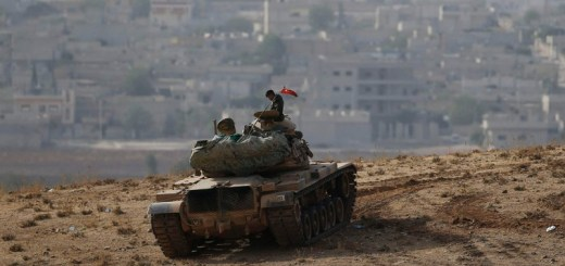 A Turkish soldier sits on top of a tank, with the Syrian town of Kobani in the background.. (photo credit:REUTERS)