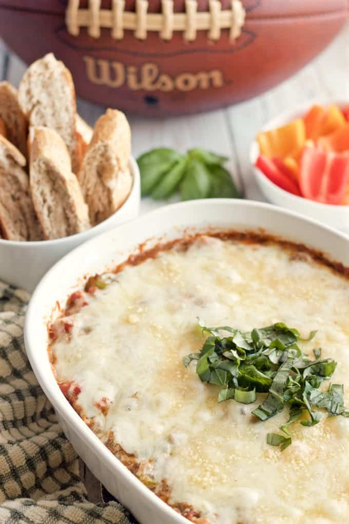 Cheesy veggie-packed pizza dip - great game day or party appetizer-- Sure to be a hit with everyone! | FamilyFoodontheTable.com