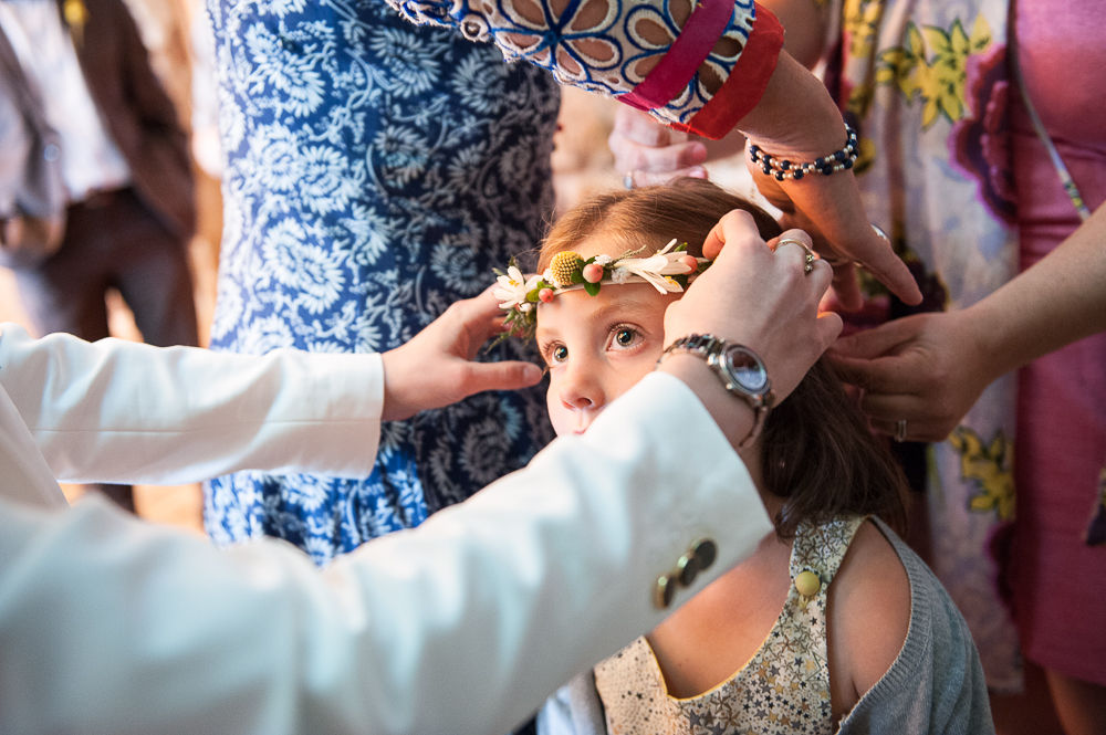 Gros plan d'une petite fille qui se fait poser une couronne de fleurs pendant les préparatifs du mariage.