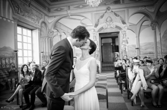Photographie du baiser des mariés à la mairie de clermont-ferrand, dans le puy-de-dome. Photo noir et blanc professionnelle style vintage par une photographe professionnelle.