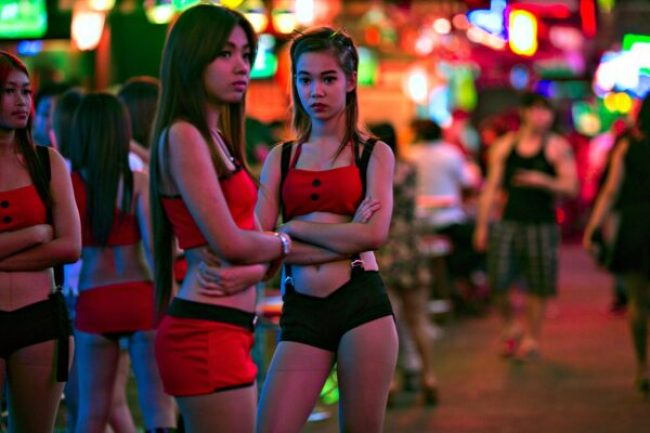 BANGKOK, THAILAND - JANUARY 21: Thai women working at a bar wait for business at the red light district called Soi Cowboy in Bangkok January 21, 2014. The popular sex tourism area filled with bars is next to an anti-government protest which has decreased their clients. Starting tomorrow the Thai government will impose the 60-day state of emergency in Bangkok and the surrounding provinces in an attempt to to cope with the on-going political turmoil. (Photo by Paula Bronstein/Getty Images)