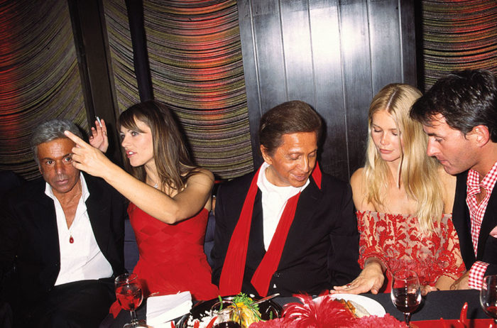 Italian fashion designer Valentino (born Valentino Clemente Ludovico Garavani) (center, with red scarf) sits at a table with, from left, his business partner Giancarlo Giammetti, British actress and model Elizabeth Hurley, and German actress and model Claudia Schiffer and her boyfiend, businessman Tim Jeffries, at the Four Seasons restaurant in New York during the Valentino Gala, New York, New York, June 14, 2000. (Photo by Rose Hartman/Getty Images)