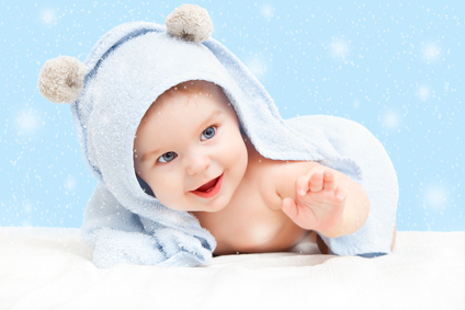 Smiling baby with towel on winter background