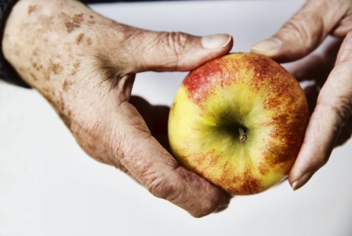 Hände einer Seniorin mit einem Apfel