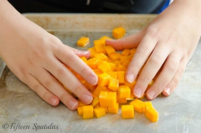tossing butternut squash cubes with maple, oil, salt and pepper