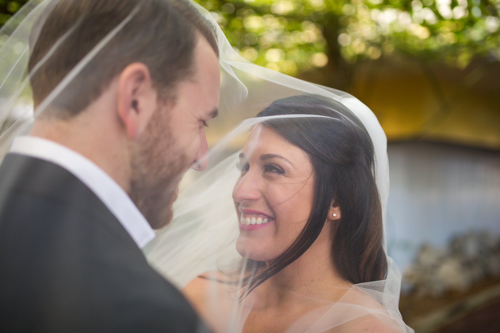 bride and groom having fun with the veil