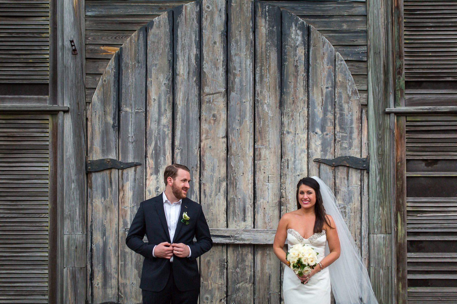 bride and groom posing in front of shipwreck museum