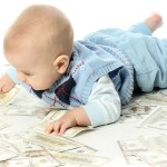 little baby lying on a pile of dollars