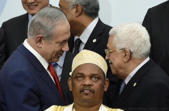 "TOPSHOTS Israeli Prime Minister Benjamin Netanyahu (L) talks with Palestine's president Mahmud Abbas (R) behind Comoros' President Ikililou Dhoinine during the family photo during the COP21, United Nations Climate Change Conference, in Le Bourget, outside Paris, on November 30, 2015. More than 150 world leaders are meeting under heightened security, for the 21st Session of the Conference of the Parties to the United Nations Framework Convention on Climate Change (COP21/CMP11), also known as ""Paris 2015"" from November 30 to December 11. AFP PHOTO / POOL / MARTIN BUREAU / AFP / POOL / MARTIN BUREAU"