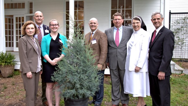 """St. Dominic's Deidre Bell and Bill Scruggs, Origin Bank's Laura Greer, FRF""""s Jim Wilkirson, Origin Bank's Larry Ratzlaff, and St. Dominic's Sister Dorothea Sondgeroth and Claude Harbarger with a cedar tree to be planted, commemorating the occasion."""