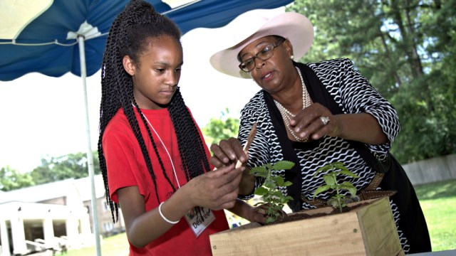 Dr. Ayers-Elliott (right) works with a camper to fillher take home planter.