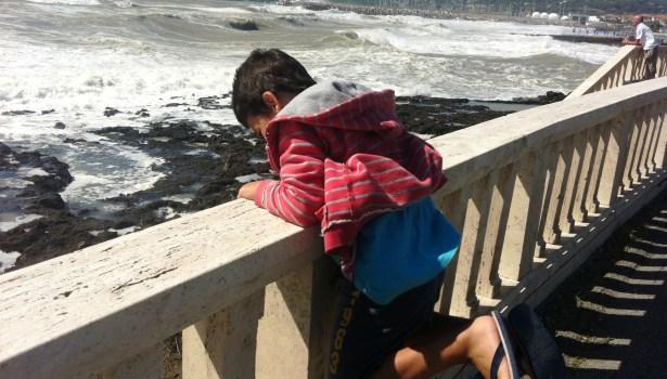Un bimbo gioca davanti alla mareggiata a Rosignano Solvay