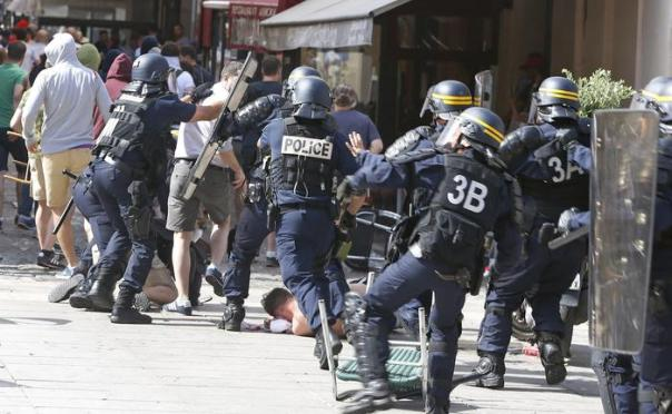 French police officers charge soccer supporters during clashes in downtown Marseille, France, Saturday, June 11, 2016. Riot police have thrown tear gas canisters at soccer fans Saturday in Marseille's Old Port in a third straight day of violence in the city. (ANSA/AP Photo/Darko Bandic)