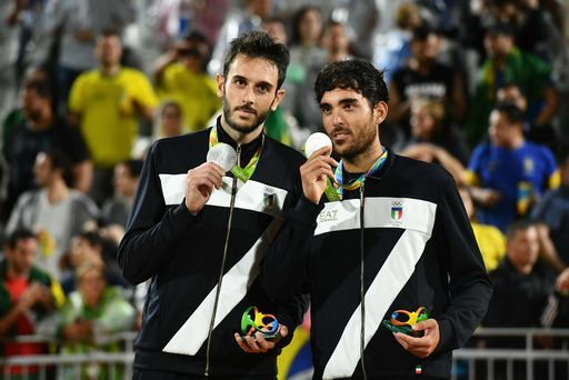 Italy's silver medallists Paolo Nicolai and Daniele Lupo celebrate on the podium at the end of the men's beach volleyball event at the Beach Volley Arena in Rio de Janeiro on August 19, 2016, during the Rio 2016 Olympic Games. / AFP PHOTO / Leon NEAL