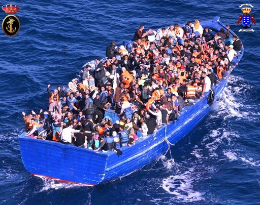 """A picture provided by Spanish Ministry of Defence on November 5, 2015 shows a boat with migrants off the coast of Libya viewed from an helicopter. A Spanish navy frigate rescued more than 500 migrants off the coast of Libya on November 5, 2015 as the small wooden fishing boat they were packed on sailed adrift, the defence ministry announced. Men, women, children and two babies, many of them wearing life jackets, were massed onto the 20-metre (66-foot) long vessel -- some perched on the edge -- in an attempt to cross the Mediterranean and reach Europe. The rescue operation lasted more than six hours, the ministry said, as soldiers from the """"Canarias"""" frigate ferried refugees to their ship on board small inflatable, motorised boats. """"The 'Canarias' frigate is headed to the Italian port of Lampedusa where the 517 immigrants on board will disembark,"""" it added. RESTRICTED TO EDITORIAL USE - MANDATORY CREDIT """"AFP PHOTO/ HO/ SPANISH MINISTRY OF DEFENCE"""" NO MARKETING NO ADVERTISING CAMPAIGNS - DISTRIBUTED AS A SERVICE TO CLIENTS"""