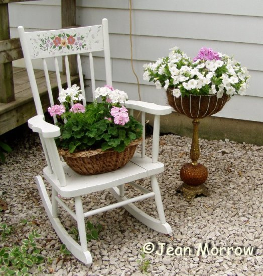 Jean Morrow's hand painted chair with baskets of pastel geranium and impatien