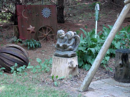 To the right of the swing, an old door, some cherubs and an orb made of rusty barrel rings.