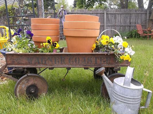 Gather up pots, soil mix, a sturdy metal stake and flowers. Thread the pole thru the pots as you stack them, filling each one with soil.