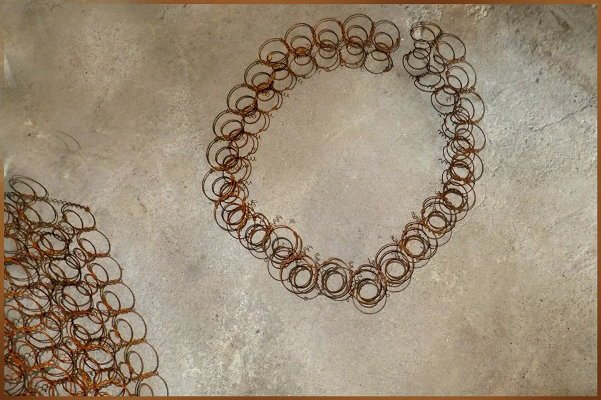 Nancy K. Meyer begins forming a wreath from her found bed springs...attch the springs with wire.