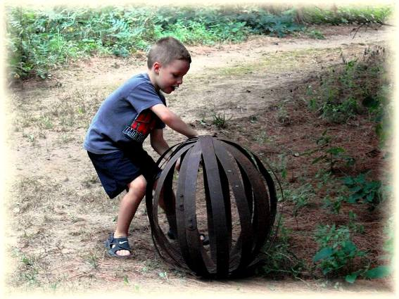 """Jeanne Sammons says, """"This is why I love Flea market gardening ... see what fun you can have ... here's that old whiskey barrel 'bands' made into a sphere and my lil' visitor this weekend enjoyed giving it a shove down the pine needle paths! I think there's six or seven here ...and Larry did this project in his shop for me, drilling holes and bolting."""