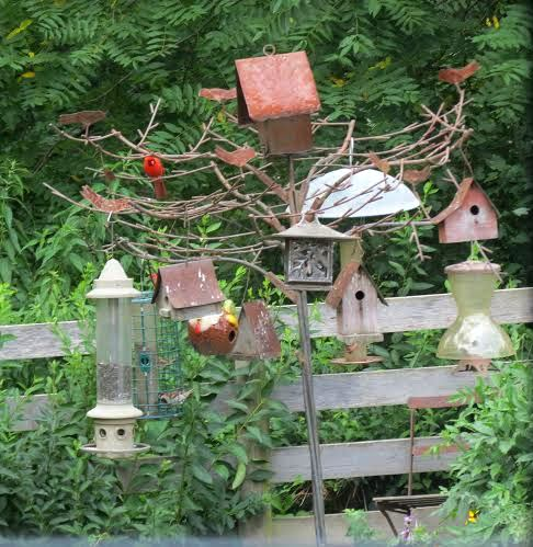 A tree sculpted from steel displays the many birdfeeders and houses near the gazebo. Can you spot the visiting cardinal?