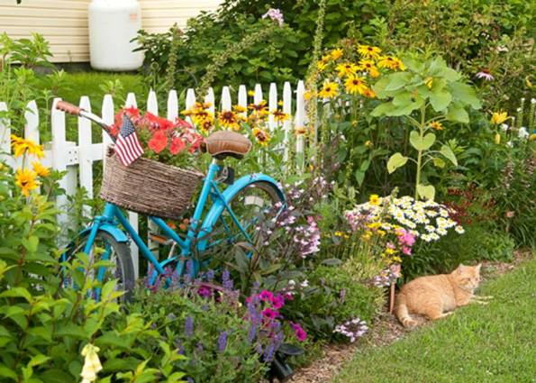 Jessica Eiss-Healthcoach blue bike contrasts with her colorful flower garden