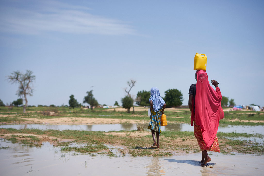 Girls carry water through a field after rain at a site of displaced civilians in Diffa, Niger, on 18 August 2016. Photo: UNICEF/Sam Phelps