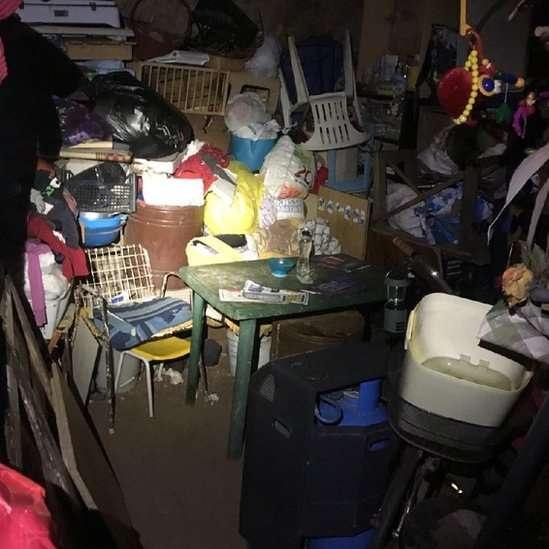 Cativeiro tinha dezenas de objetos acumulados, restos de comida, latas com excrementos e um colchão no chão, onde a jovem dormia com os filhos | Fonte: Polícia italiana © BBC