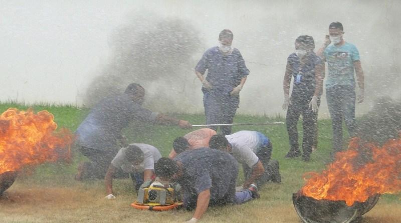"""Ediane Mariano é auxiliar administrativa do Serviço de Atendimento ao Usuário (SAU), do Hospital Regional Público da Transamazônica (HRPT), em Altamira, no sudoeste do Pará. Mas, na última semana, ela participou de funções bem diferentes das habituais, como fechar o registro de um botijão de gás pegando fogo, apagar chamas usando o extintor de incêndio e realizar o resgate e o transporte de vítimas. A auxiliar e outros 110 colaboradores da unidade passaram pelo Curso de Formação da Brigada de Incêndio no início deste mês, no Hospital Regional Público da Transamazônica. Os novos brigadistas foram divididos em quatro turmas e aprenderam noções básicas de combate a incêndio e socorro às vítimas em caso de sinistro na unidade. Foram ministradas aulas teóricas sobre primeiros socorros, evacuação, método de avaliação de múltiplas vítimas, além da parte prática, com simulações de situações de sinistro. Quem participou do curso, aprovou. """"É importante, sobretudo a prática, porque vivenciamos situações de emergência, testamos nossas habilidades e aprendemos a manusear os equipamentos necessários. Caso haja um princípio de incêndio na unidade, estamos aptos e capacitados a identificar as situações de emergência, combater o fogo, promover a evacuação e prestar os primeiros socorros às vítimas, cumprindo com segurança todos esses procedimentos"""", afirmou Ediane.  FOTO: ASCOM / HRPT DATA: 06.03.2018 ALTAMIRA - PARÁ"""