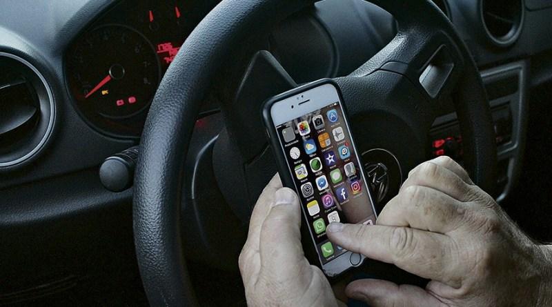 destaque-511590-celular-no-volante-carro-dirigindo-hiran-haun