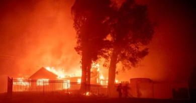 (FILES) In this file photo taken on October 31, 2019 a firefighter works the scene as wind-whipped flames and embers light multiple homes on fire during the Hillside fire in the North Park neighborhood of San Bernardino, California. - US President Donald Trump threatened once again on November 3, 2019 to withhold federal aid from California after its Democratic governor criticized his environmental policies.Over the past two weeks, fires have ravaged nearly 100,000 acres (40,000 hectares) in the sprawling western state, where fighters on Sunday were battling the Maria Fire, about 60 miles northwest of Los Angeles. (Photo by Josh Edelson / AFP)