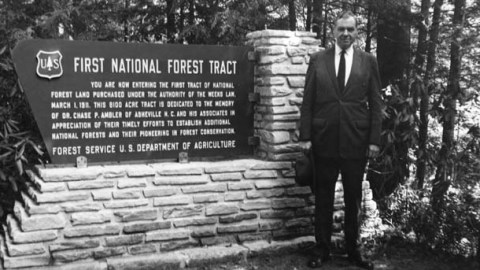 Forest Service chief Richard E. McArdle standing beside the sign marking the first forest tract purchased under the Weeks Act.