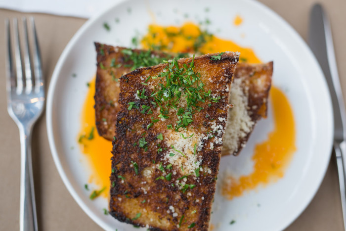 Roustabout's garlic bread features thick, crusty slabs of house made bread bathed in garlic butter and Calabrian chile-infused oil. (Photo credit: Roustabout)