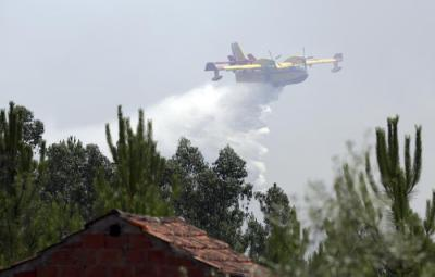 A firefighting airplane drops its load of water trying to prevent a forest fire from reaching the village of Ouzenda, outside Pedrogao Grande, central Portugal, Tuesday, June 20 2017. Ouzenda residents were evacuated and firefighters moved in to protect the houses while aircraft battled the fire approaching the small village. Emergency services in Portugal said Tuesday they were making headway in their battle to control a major wildfire that killed more than 60 people in the central region of the country. (ANSA/AP Photo/Armando Franca), [CopyrightNotice: Copyright 2017 The Associated Press. All rights reserved.]