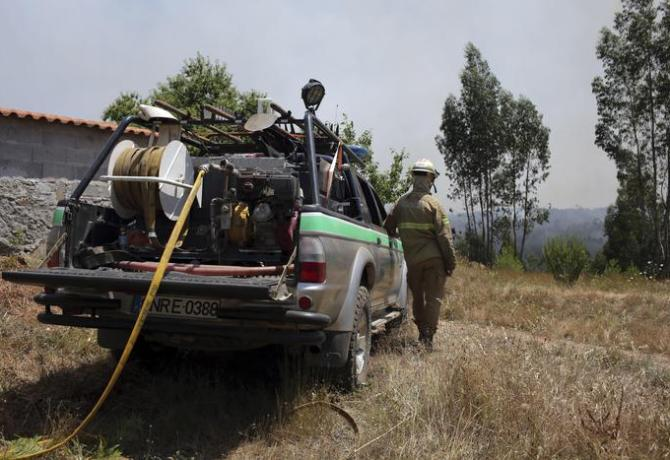 A Portuguese National Republican Guard firefighter keeps watch on a forest fire burning near the village of Ouzenda, outside Pedrogao Grande, central Portugal, Tuesday, June 20 2017. Ouzenda residents were evacuated and firefighters moved in to protect the houses while aircraft battled the fire approaching the small village. Emergency services in Portugal said Tuesday they were making headway in their battle to control a major wildfire that killed more than 60 people in the central region of the country. (ANSA/AP Photo/Armando Franca) [CopyrightNotice: Copyright 2017 The Associated Press. All rights reserved.]
