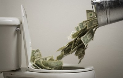 Person dumping money into a toilet bowl --- Image by © Rubberball/Corbis