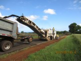 A cold plane machine shoots granules of the old grounded up asphalt from Kapaka Road into a trailer.