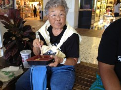 Joanne Watanabe enjoys a plate lunch at the Honolulu airport.