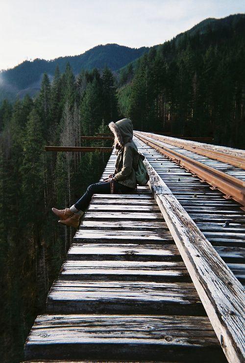 gril sitting on bridge