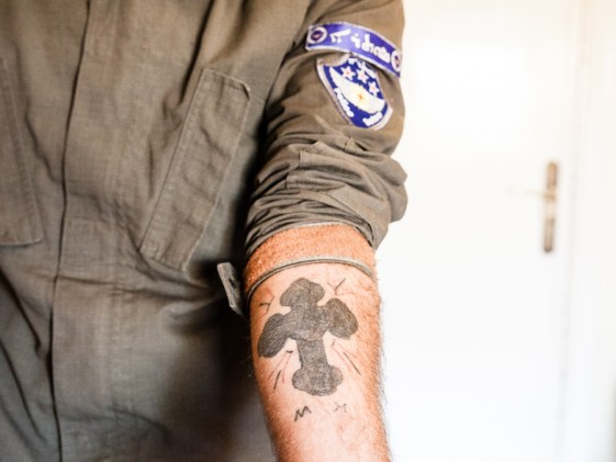 A cross is tattooed on the arms of a Sutoro member. With tattoos such as this fighters are proudly declaring their affiliation and commitment to their community, for if they are captured by Jihadists, there is no denying their religion.