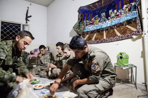 Syriac Sutoro soldiers eat under a tapestry displaying the last supper biblical scene. South of Tirbespiyeh, Syria, June 2014