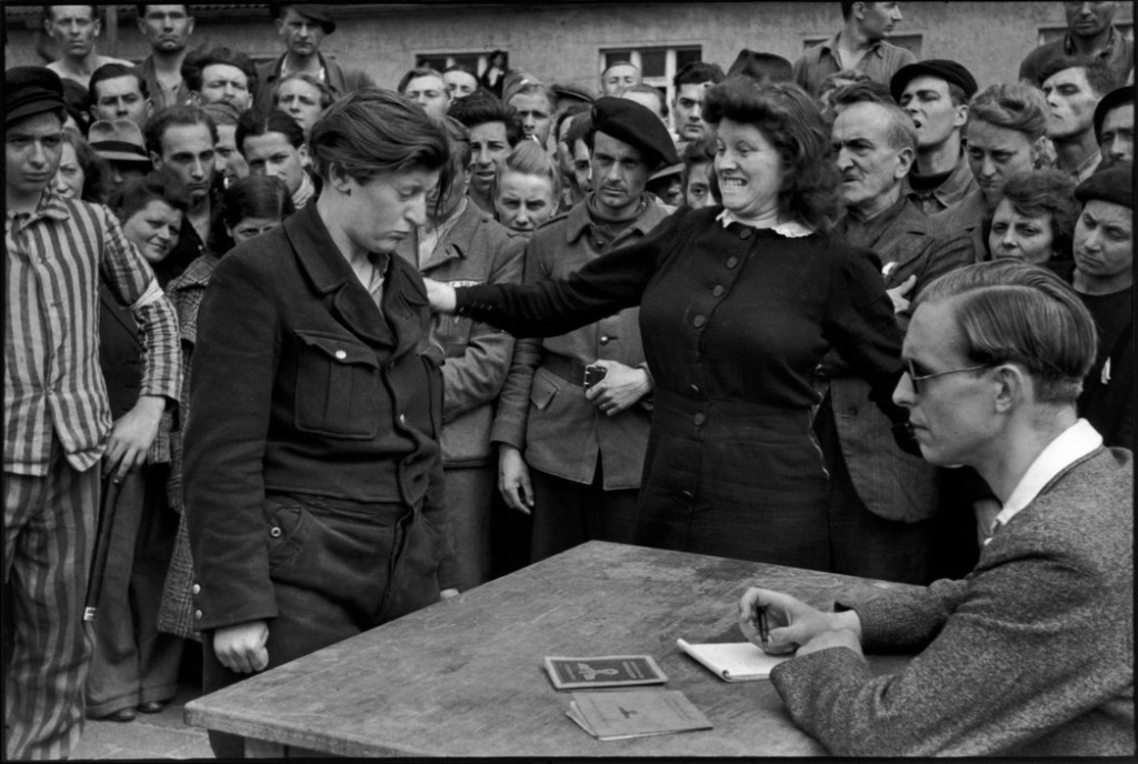 GERMANY. Dessau. A transit camp was located between the American and Soviet zones organised for refugees; political prisoners, POW's, STO's (Forced Labourers), displaced persons, returning from the Eastern front of Germany that had been liberated by the Soviet Army. A young Belgian woman and former Gestapo informer, being identified as she tried to hide in the crowd. April 1945.