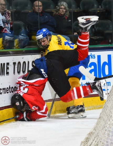 Sweden's Erik Brannstrom #14 and Canada's Michael McLeod #22 collide at the boards during semifinal round action at the 2016 IIHF Ice Hockey U18 World Championship. (Photo by Matt Zambonin/HHOF-IIHF Images)