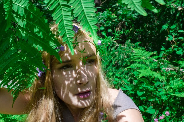 Pastel haired fairy stares off to distance through shaddow play of fern leaves