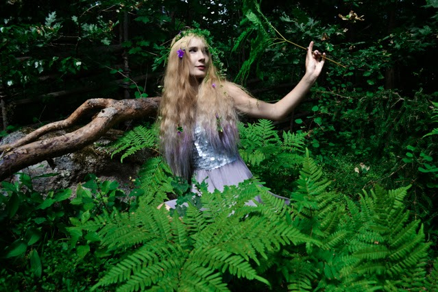 Purple pastel haired fairy rises from surrounding greenery
